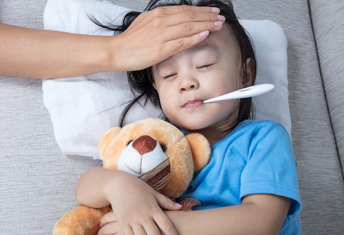 sick child with thermometer in mouth and nurse hand on forehead